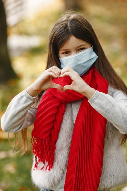 Bambino in piedi nella sosta di autunno. tema coronavirus. ragazza in una sciarpa rossa. Foto Gratuite