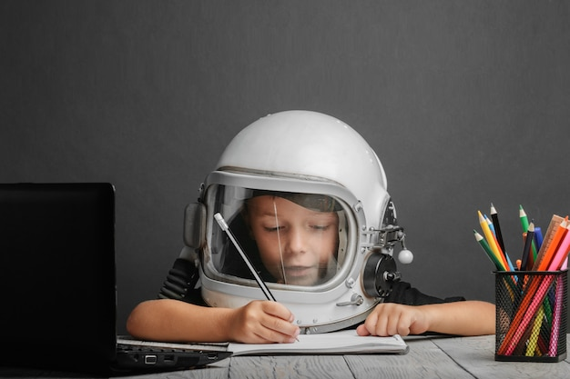 The child studies remotely at school, wearing an astronaut's helmet. back to school Premium Photo