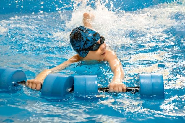 Детское плавание с водными гантелями в руках в бассейне Premium Фотографии