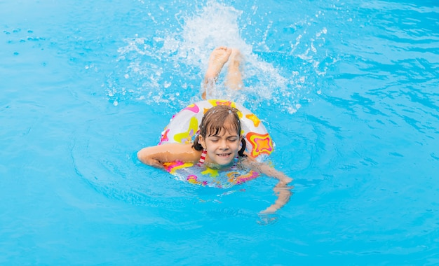 The child swims in the pool in the summer. Premium Photo