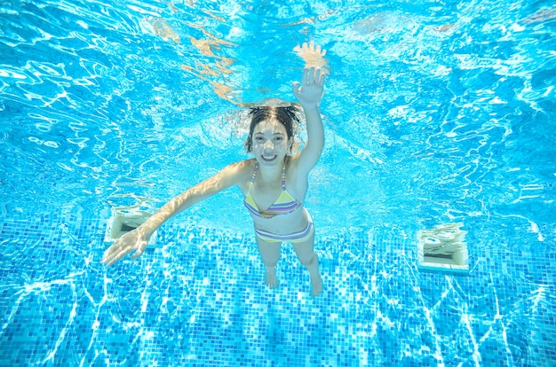 Child swims underwater in swimming pool, happy active teenager girl dives and has fun under water, kid fitness and sport on family vacation on resort Premium Photo