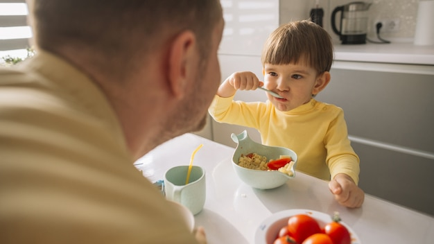 Child taking cereals from the bowl and eats Free Photo
