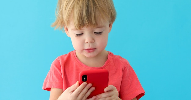 Child tapping cell phone screen, interest in modern technology Premium Photo