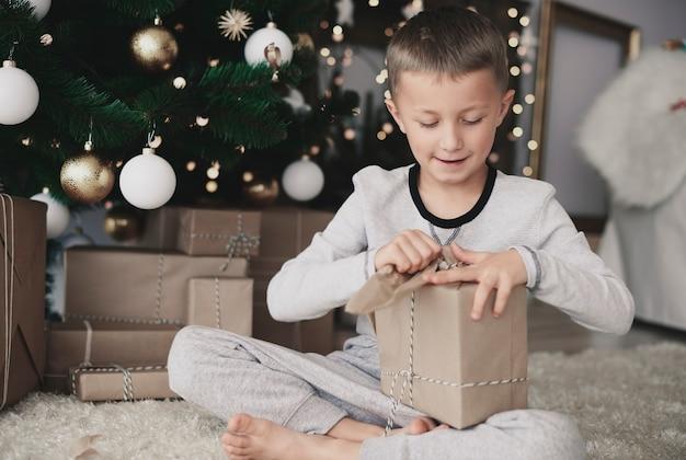 Ребенок рвет рождественскую бумагу Бесплатные Фотографии