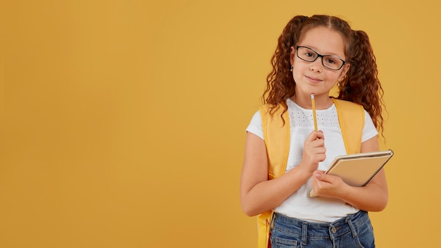 Child thinking and holding notebook copy space Premium Photo