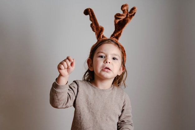 Child toddler with deer headband at home with exited funny face. christmas new year holidays Premium Photo