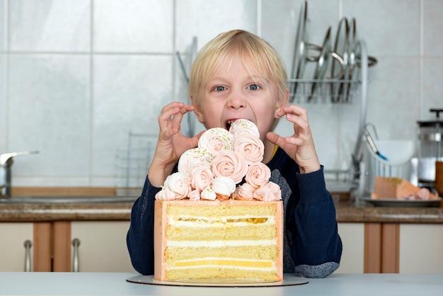 子供はケーキを食べたいです。子供は貪欲にケーキを見ます。 Premium写真