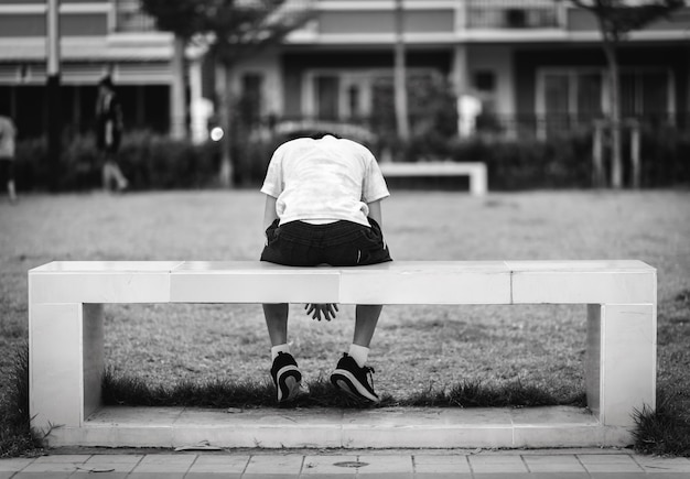 The child was sitting in a sad square chair at a park Premium Photo