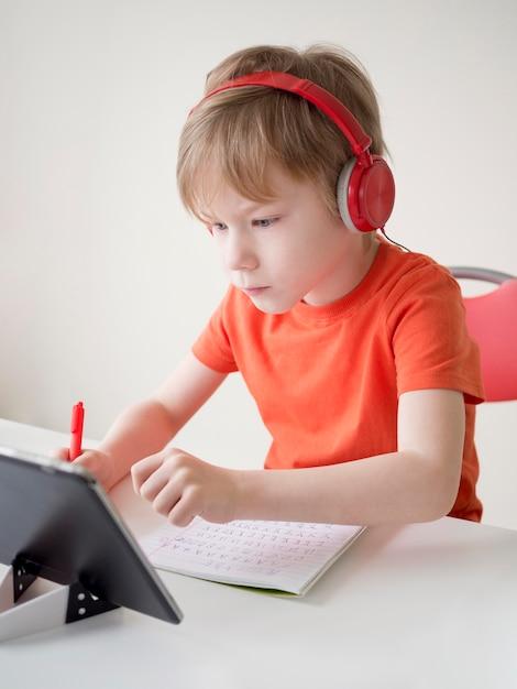 レッスンを理解しようとするヘッドフォンを身に着けている子供 無料写真