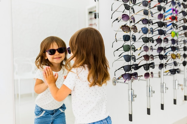 Child wearing sunglasses and looking in mirror Free Photo