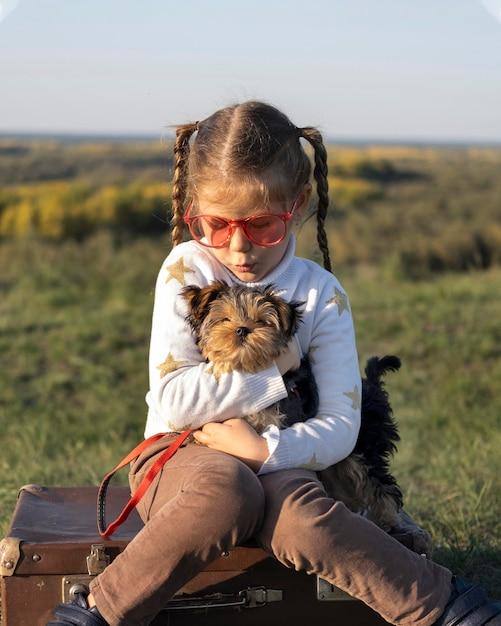 Ребенок в солнцезащитных очках играет со своей собакой, вид спереди Бесплатные Фотографии