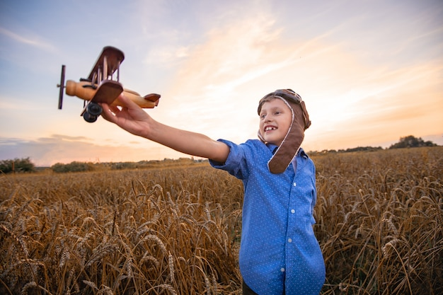 Child in a wheat field in the village with a retro plane in his hands Premium Photo