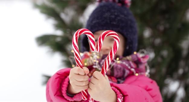 ぼやけた背景に大きなキャンディケインを持つ子供。冬の休日のコンセプト。 無料写真