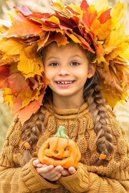 Ребенок с венком на голове и тыквой в руках на хэллоуин. Premium Фотографии