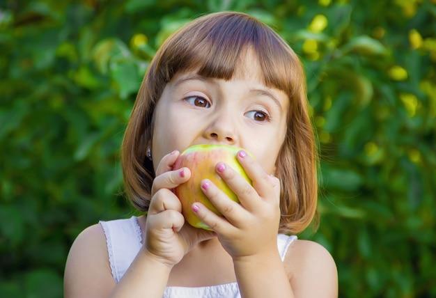 Ребенок с яблоком. выборочный фокус. природа Premium Фотографии
