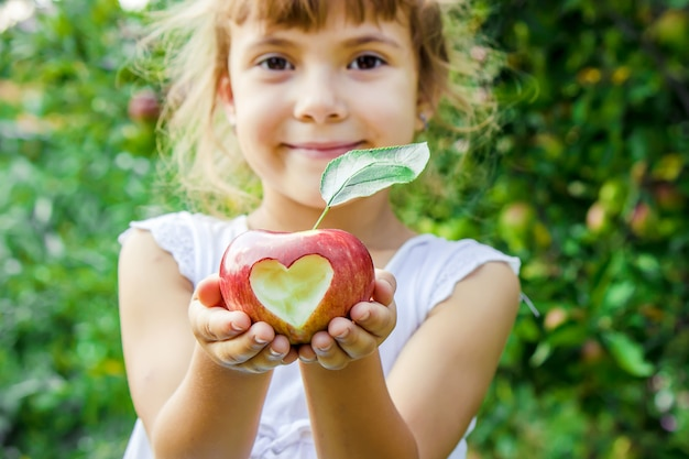 Child with an apple. selective focus. garden. Premium Photo