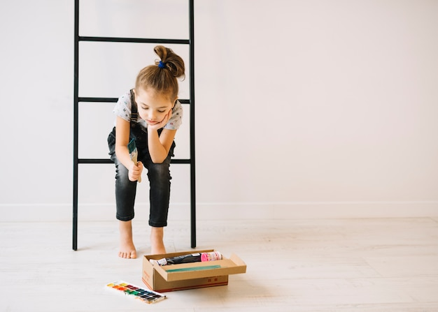 Child with brush sitting on ladder near wall and box with colors on floor Free Photo
