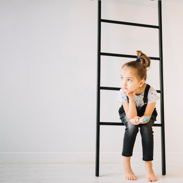Child with brush sitting on ladder near wall in room Free Photo
