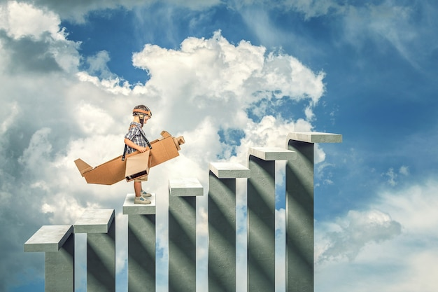 Child with cardboard airplane on abstract concrete stair Premium Photo