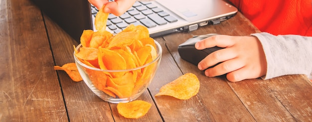 Child with chips behind a computer. selective focus. Premium Photo