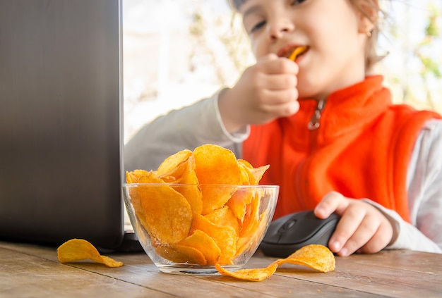 Child with chips behind a computer Premium Photo