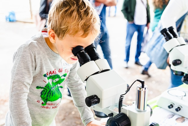 Child with curiosity during a medicine fair looking at bacteria through a microscope Premium Photo