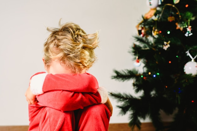 Child with disguise, anxious and sad on christmas day with an angry face next to the christmas tree while waiting for santa Premium Photo