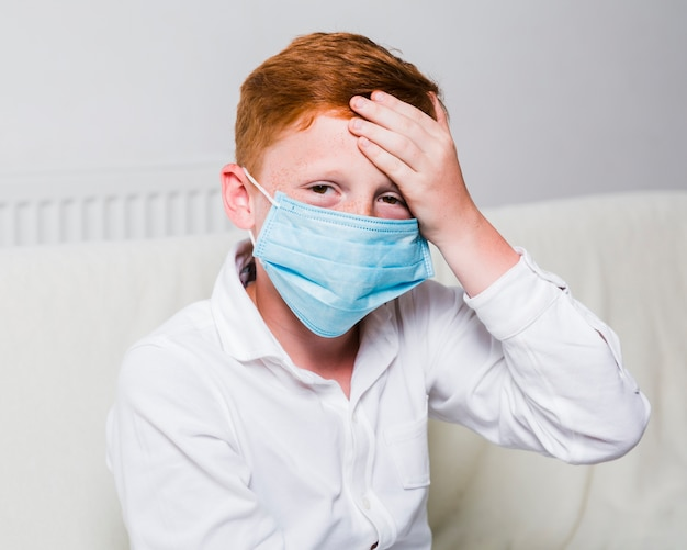 Child with face mask and headache Free Photo
