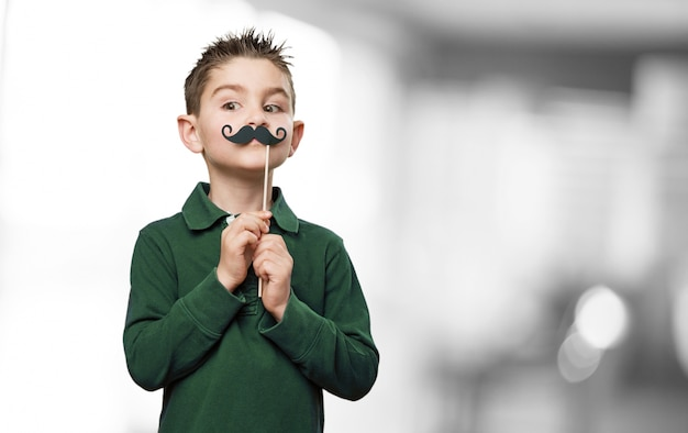 Child with a fake mustache Free Photo