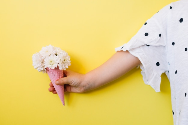 Child with flowers in cone Free Photo