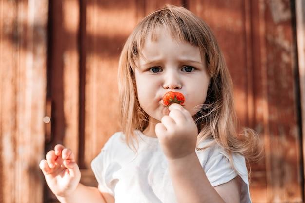 食べ物を持つ子供。いちごを健康的に食べる。 Premium写真