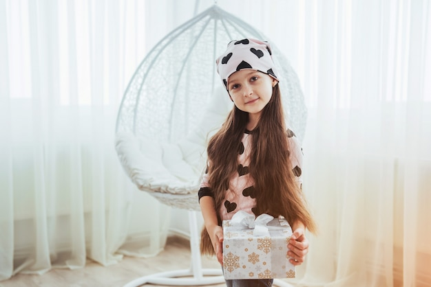 A child with a gift in a beautiful bright studio. Premium Photo