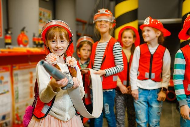 消防士の手にホースを持つ子供 Premium写真
