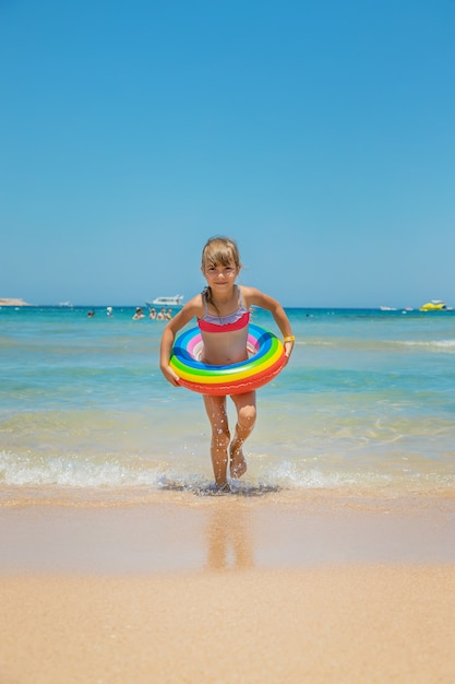 Child with a life buoy at sea Premium Photo