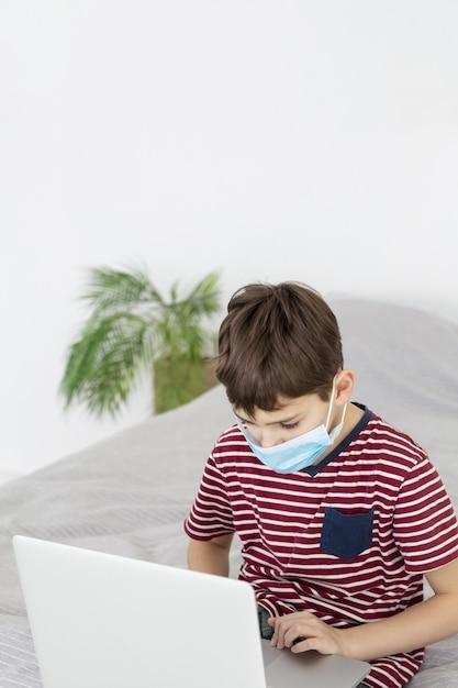 ノートパソコンを見て医療マスクを持つ子供 無料写真