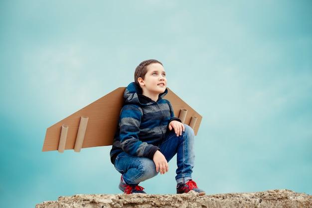 紙飛行機の翼を持つ子供 Premium写真