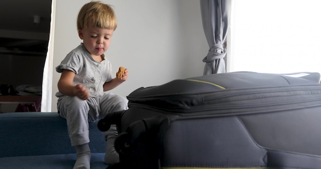 Childe is sitting and eating cookies next to a suitcase Premium Photo