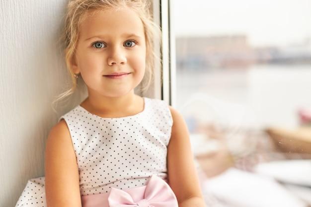 子供の頃と無実の概念。幸せな表情と笑顔を持って窓際に座っている金髪と大きな美しい目が集まった魅力的なかわいい女の子の肖像画 無料写真