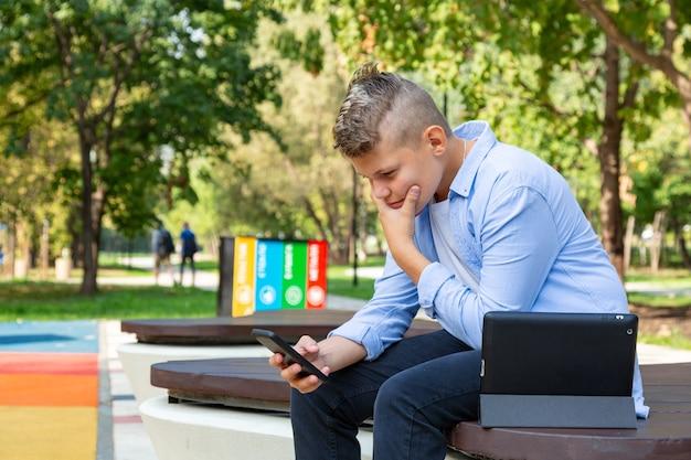 Детство, дополненная реальность, технологии и люди концепции - мальчик с озадаченным лицом смотрит в смартфон на открытом воздухе летом Premium Фотографии
