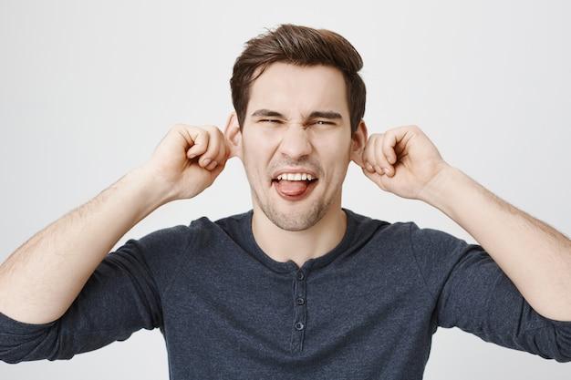 幼稚な面白い男の耳を引っ張ると舌を見せて、しかめっ面 無料写真