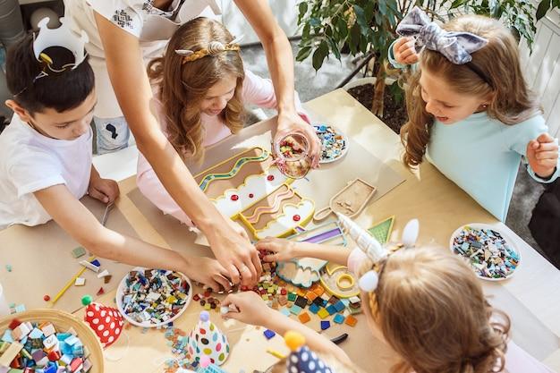 子供と誕生日の飾り。食べ物、ケーキ、飲み物、パーティーガジェットを備えたテーブルセッティングの男の子と女の子。 無料写真
