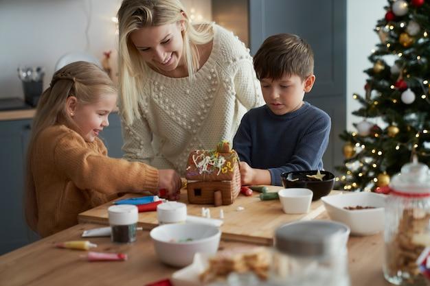 Дети и мама украшают пряничный домик на кухне Бесплатные Фотографии
