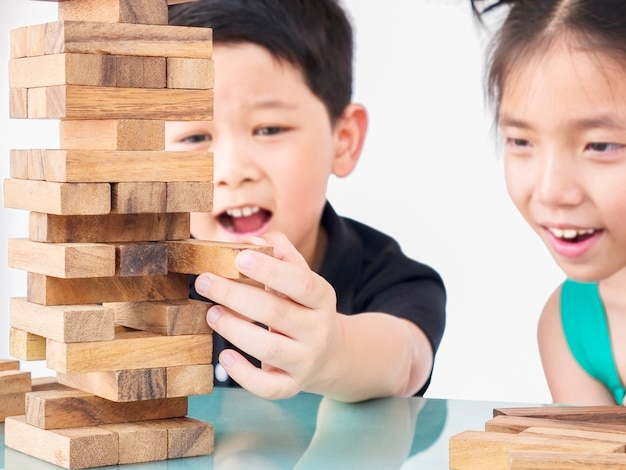 Children are playing jenga, a wood blocks tower game Free Photo