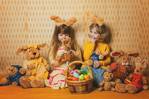 Children are sitting on a blanket amid the easter hares  vintage style. Premium Photo