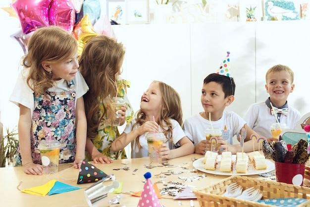 Bambini e decorazioni di compleanno. ragazzi e ragazze a tavola con cibo, dolci, bevande e gadget per le feste. Foto Gratuite