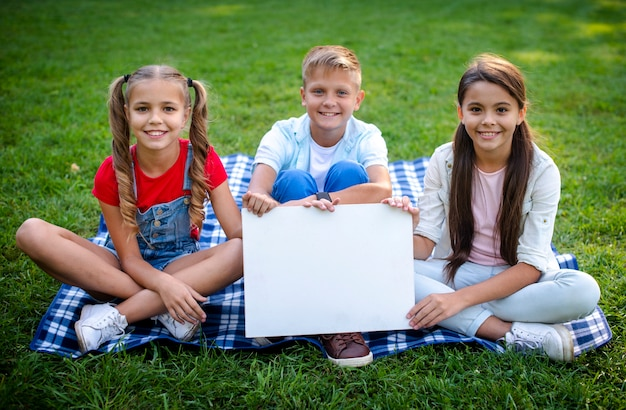 Children on blanket holding a poster in hands Free Photo