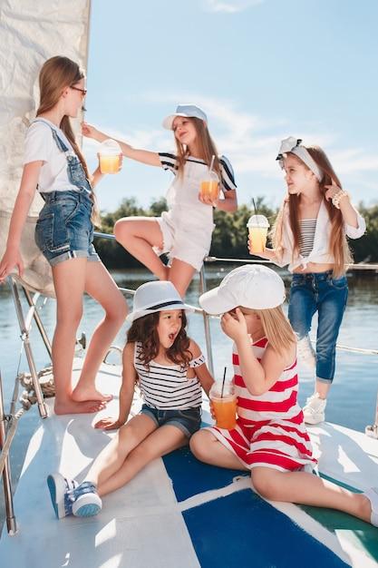 I bambini a bordo dello yacht del mare bevono succo d'arancia. le ragazze adolescenti o bambini contro il cielo blu all'aperto. vestiti colorati. concetti di moda per bambini, estate soleggiata, fiume e vacanze. Foto Gratuite