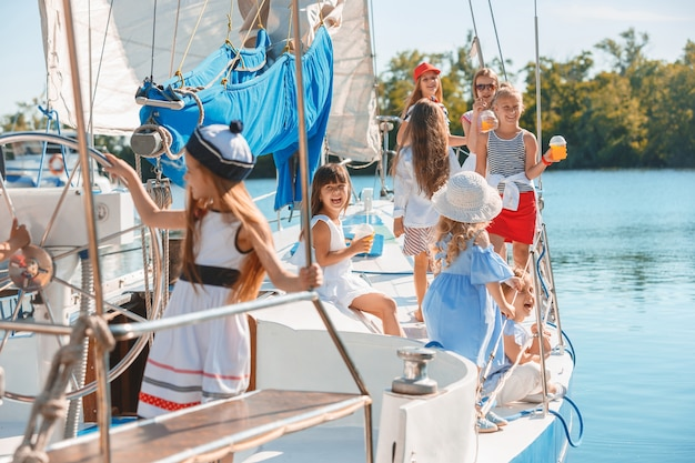 The children on board of sea yacht drinking orange juice. the teen or child girls against blue sky outdoor. Free Photo