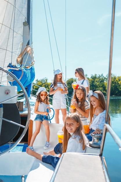 I bambini a bordo dello yacht del mare bevono succo d'arancia Foto Gratuite