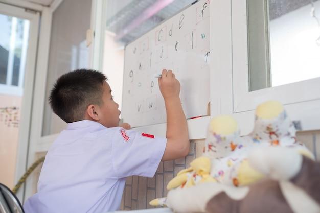 Children boy doing homework, kid write paper Premium Photo